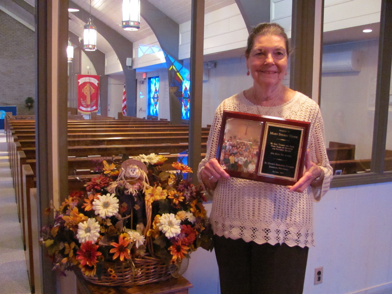 A parishioner is honored for years of faithful service as she moves away